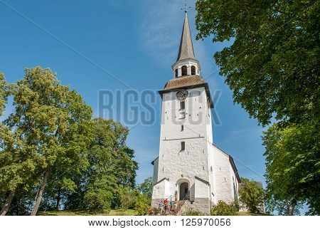 MARIEFRED, SWEDEN - AUGUST 4: Tourists visit Mariefred church on August 4, 2011 in Mariefred. This historic idyllic small town on Lake Mälaren is a popular tourist destination during summer