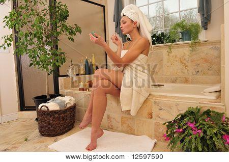 Woman Fixing Lipstick In The Bathroom