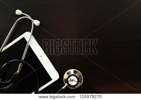 Stethoscope and tablet on dark wooden background
