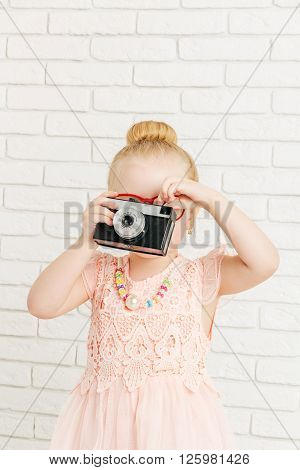 Little girl with retro camera in hand. Closeup