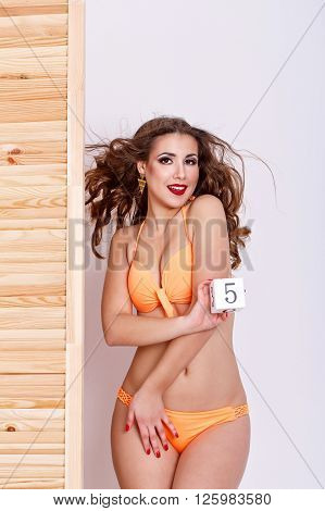 Slender attractive girl in a swimsuit. Girl holds in the hands of the figure five. Shopping. Preparation for the beach season. poster
