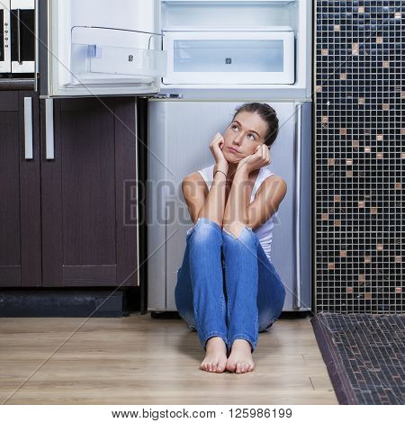 Portrait of unhappy and hungry girl near empty fridge