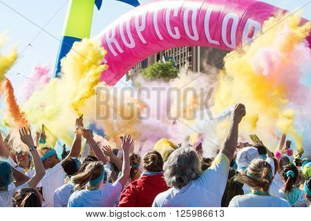 HAMPTON, GA - APRIL 2016: A crowd of runners who completed the Color Run toss packets of colored corn starch into the air creating an organic explosion of colors over the group in Hampton GA on April 2 2016 .
