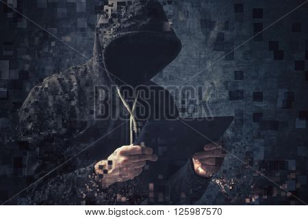 Unrecognizable faceless hooded cyber criminal man using digital tablet to access internet.