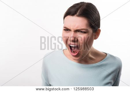 Obsessed with emotions. Irritated emotional beautiful girl screaming and  expressing anger while standing isolated on grey background
