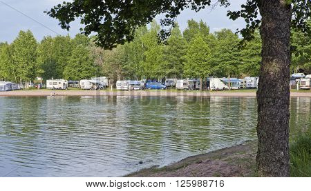 RAUMA, FINLAND ON JULY 01. View of a Camp, Camping grounds along the seaside on July 01, 2013 in Rauma, Finland. Caravans and Campers. Unidentified people on the shore. Editorial use.