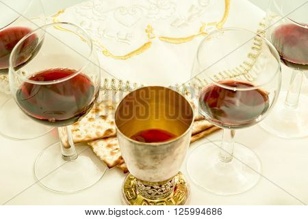 the symbols of the feast of Passover; three pieces of matzah; poured a glass of red wine; white cloth with embroidery and font on the Hebrew Pesach; on a white background; isolated;