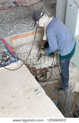 Builder destroys cement stairs with a jackhammer