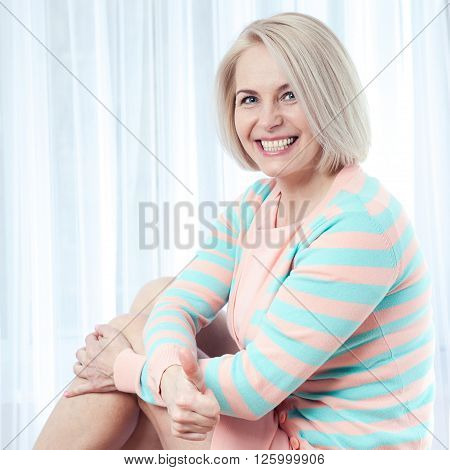Active beautiful middle-aged woman smiling amiably showing thumbs up and looking at camera.