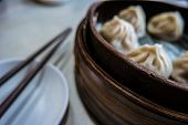 Traditional chinese food, steamed dumpling served on table in a wooden dish and with wooden chopsticks. poster