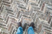 Feet of an urbanite man in jeans standing on old cobblestone pavement poster
