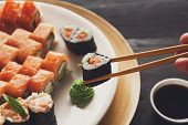 Eating sushi rolls. Japanese food restaurant, sushi maki gunkan roll plate or platter set. Closeup of hand with chopsticks taking roll. Ginger, soy, wasabi. Sushi at black rustic wood background. poster