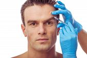 Portrait of handsome man having injections of botox isolated on white background poster