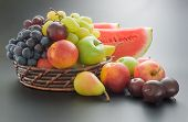Various fresh ripe fruits arranged in a wicker basket and around on neutral gray gradient background poster