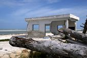 a storm shattered house sits on an idyllic beach poster