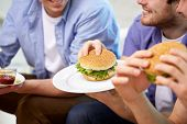 fast food, unhealthy eating, people and junk-food - close up of happy friends eating hamburgers at home poster