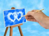 hand with brush blue sky and heart-shaped clouds on easel poster
