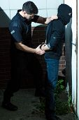 Photo of handcuffing wanted criminal by policeman poster
