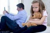 young internet addict father using mobile phone ignoring little sad daughter looking bored hugging teddy bear abandoned and disappointed with her dad in parent bad selfish behavior poster