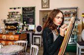 Hipster artist paints a painting in defocused cafe interior. Closeup of painting process in light art workshop interior. Creative  studious hipster woman painter paints in her studio picture. poster