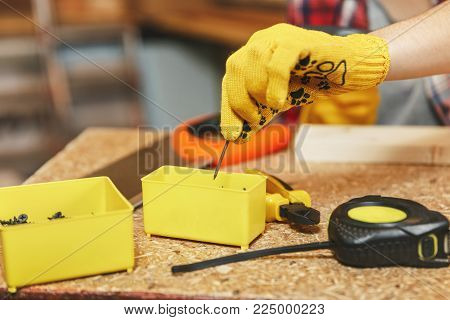 Close up of woman hand in yellow glove takes a nail from the box. Work in carpentry workshop at wooden table place with piece wood, different tools like saw, tape measure, box with screws