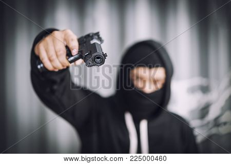 Masked robber with gun aiming into the camera with monochrome background. Dangerous gun man as bandit.