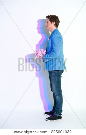 Full length side view serene male with multicolored shadow holding nosegay. Anticipation concept