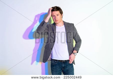 Portrait of assertive modern male touching hair by hand. Assurance concept