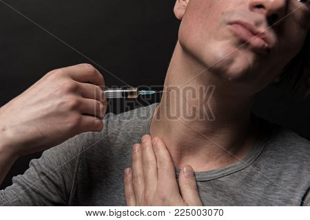Close up of addict person inserting needle into his neck. Isolated on background