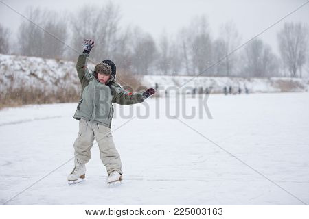 The kid learn to skate. The boy on the lake in winter snowy day on skates. Skating on the lake