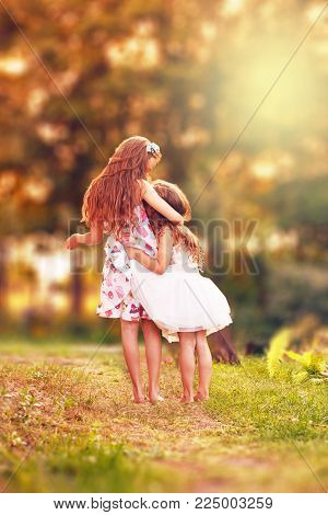 Two Happy little girl embracing and smiling at summer day, back view
