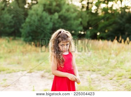 Portrait of cute sad little girl looking worried  at summer day