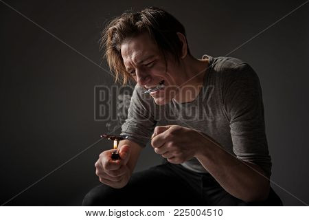 Man in narcotic withdrawal using lighter for preparing drug dose. Isolated on background