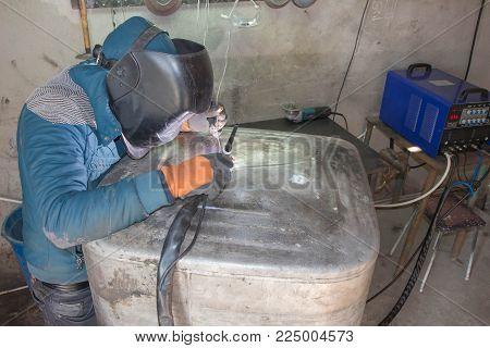 Worker welding aluminum using tig welder. Argon aluminum welding