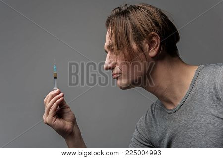Side view profile of serious man with drug addiction. He is holding and looking at injector. Isolated on background poster