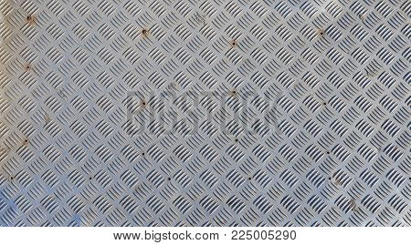 A background of metal diamond plate close up.