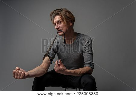 Impatient addicted man piercing a needle in the hand. He is looking at camera with pain in eyes. Isolated on background
