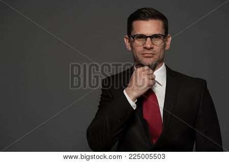 Portrait of successful businessman in formal attire and glasses correcting his necktie looking at the camera on gray background. Place for text
