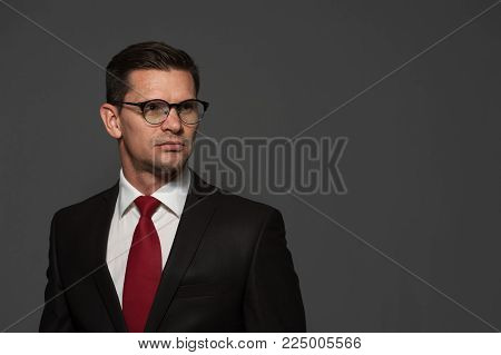 Portrait of positive businessman in formal attire and glasses looking to the side on gray background. Place for text.