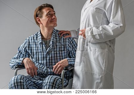 Young man with musculoskeletal disease sitting in wheelchair and smiling to nurse. She is holding hand on his shoulder. Isolated on background