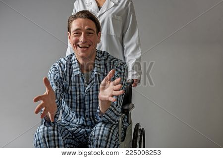 Portrait of happy patient sitting in means for movement of invalids. Medical assistant is standing behind him. Copy space in right side. Isolated on background