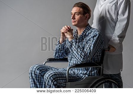 Thoughtful man having physical inability to move. Nurse is treating him. Isolated on background