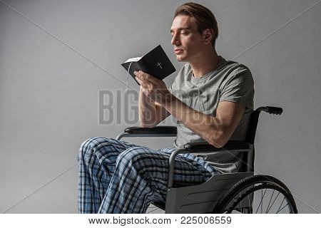 Tranquil invalid with bible turning to god with prayer. Isolated on background