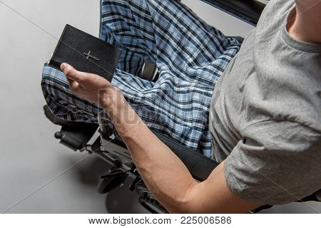 Top view of paralyzed desperate male person in wheelchair with holy writ in hand
