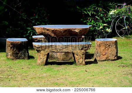 marble chair on grass in garden have bush tree  background.