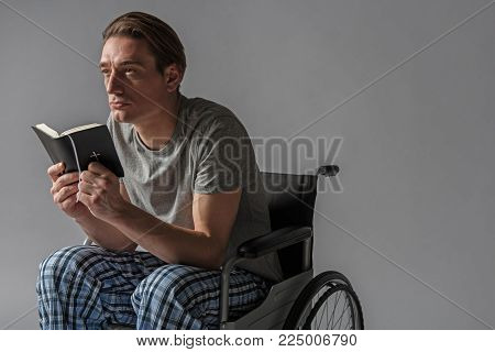 Thoughtful unhealthy man sitting in wheelchair with holy book in hands. Copy space in right side. Isolated on background