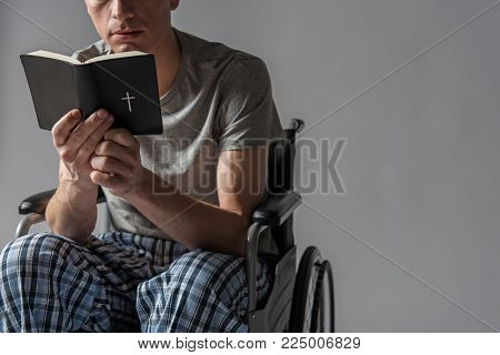 Spirituality concept. Calm disabled man reading bible. Copy space in right side. Isolated on background