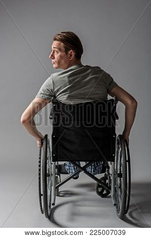 Back of sad unhealthy male person sitting in the vehicle for disabled. Health concept