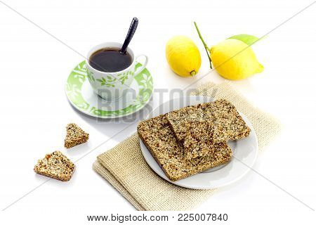 National, traditional, Greek sweets (pasteli) from honey, sesame, poppy seed and lemon rind and cup with tea on white background close-up.