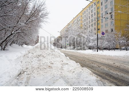 A big pile of snow on the city road. Winter in Russia.